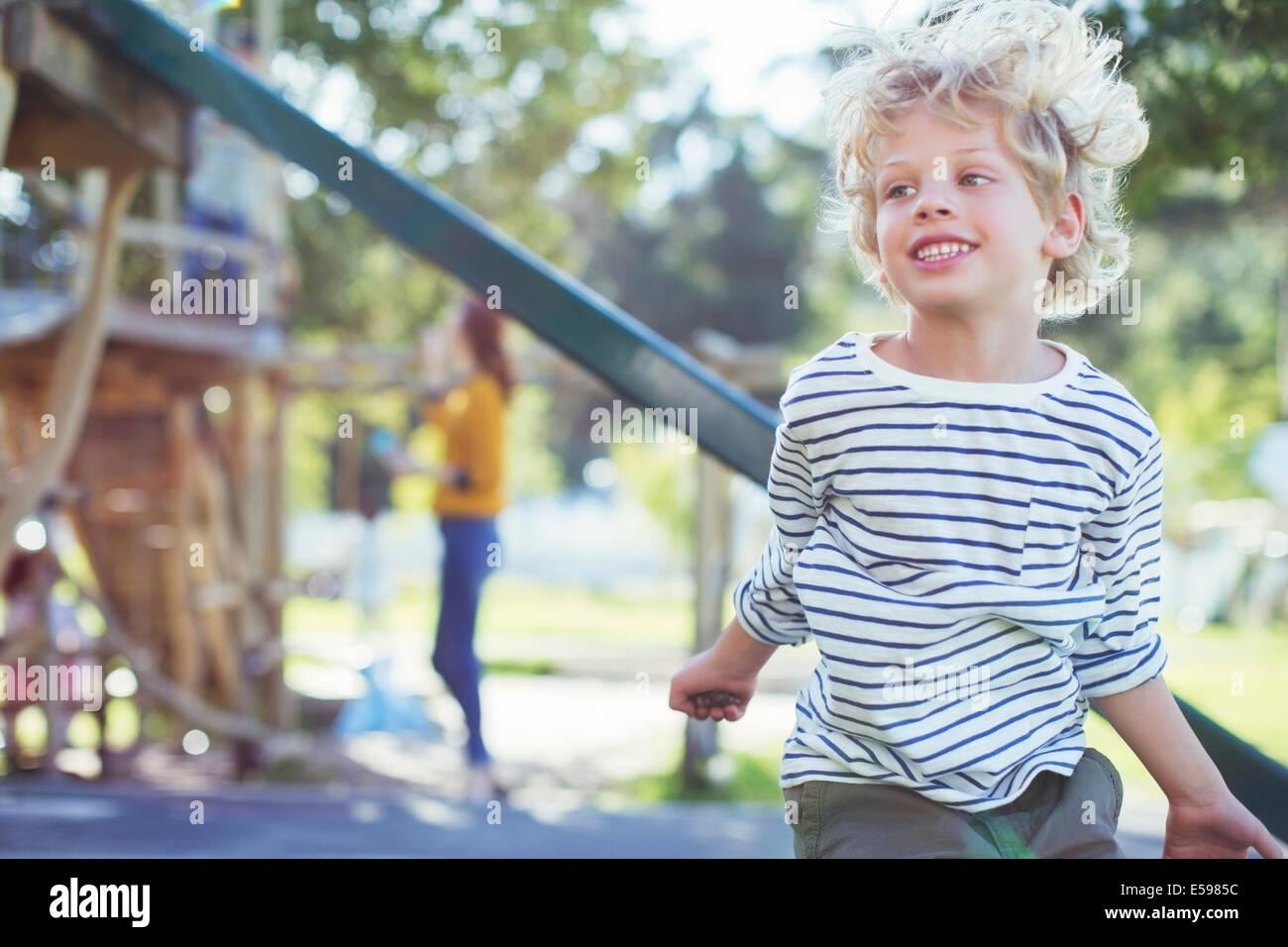 Junge spielt auf Spielplatz Stockfoto