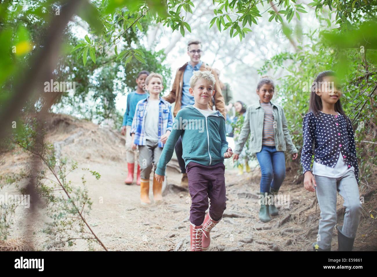 Schüler und Lehrer, die zu Fuß in Wald Stockfoto