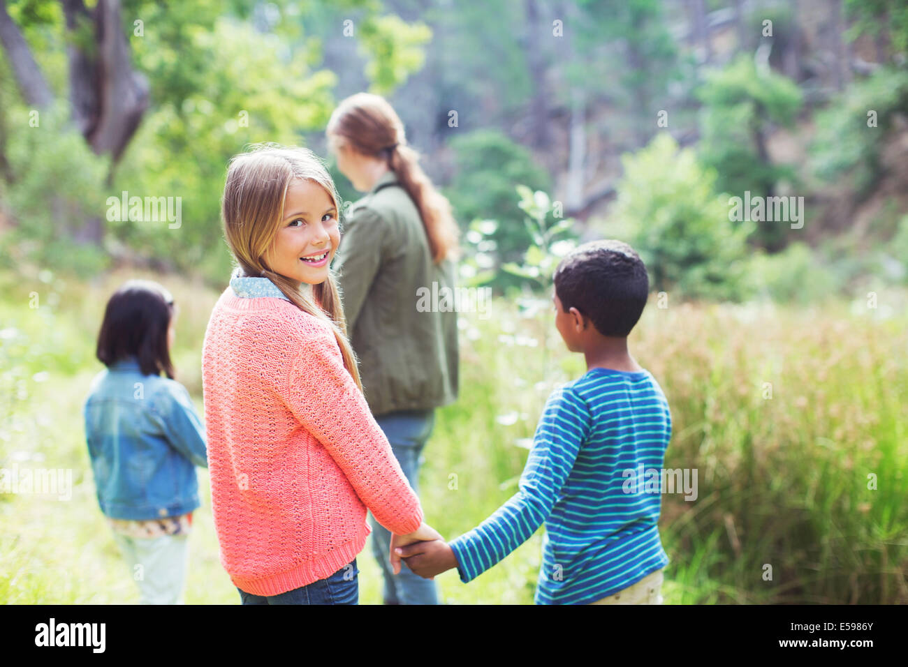 Kinder Hand in Hand im Bereich Stockfoto