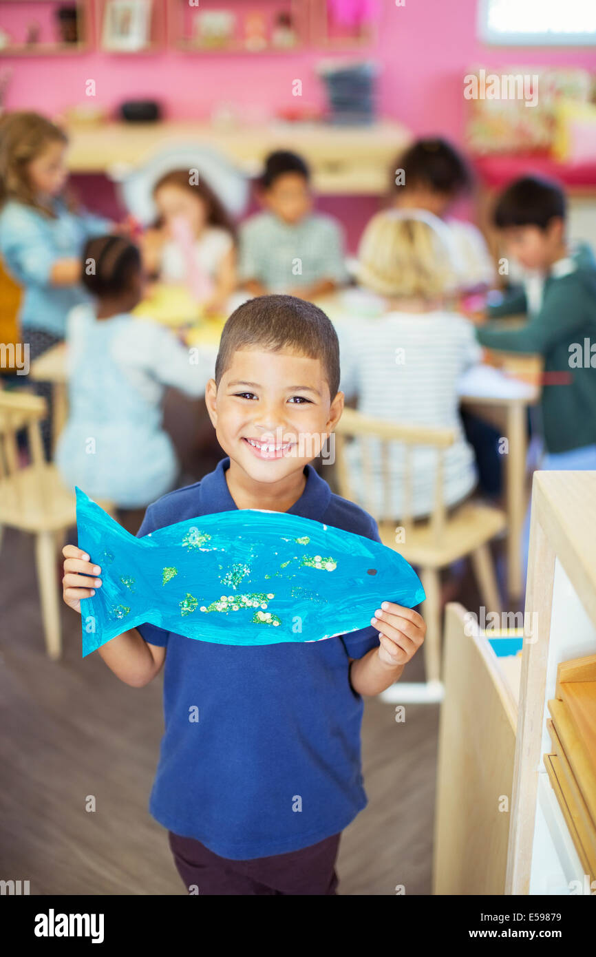 Schüler halten malte Fische im Klassenzimmer Stockbild