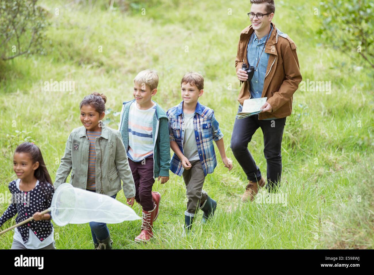 Schüler und Lehrer, die zu Fuß in Feld Stockbild