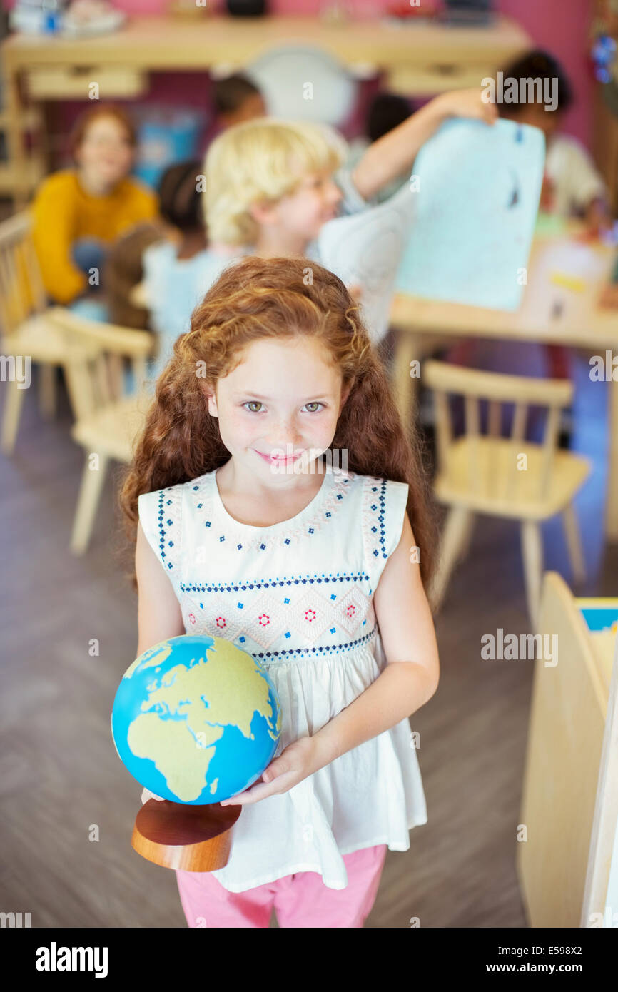 Schüler halten Globus im Klassenzimmer Stockbild