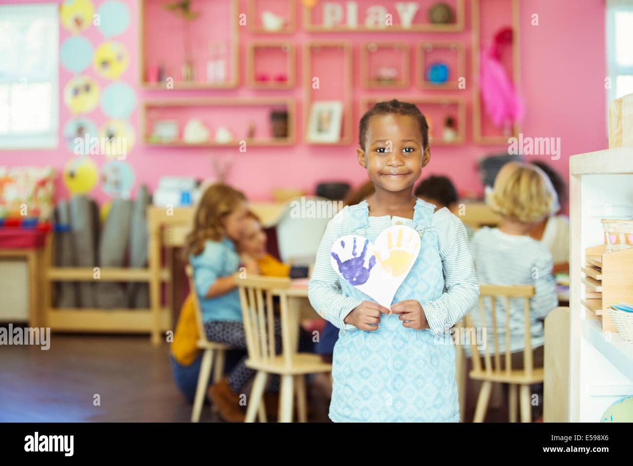 Schüler halten Malerei im Klassenzimmer Stockbild