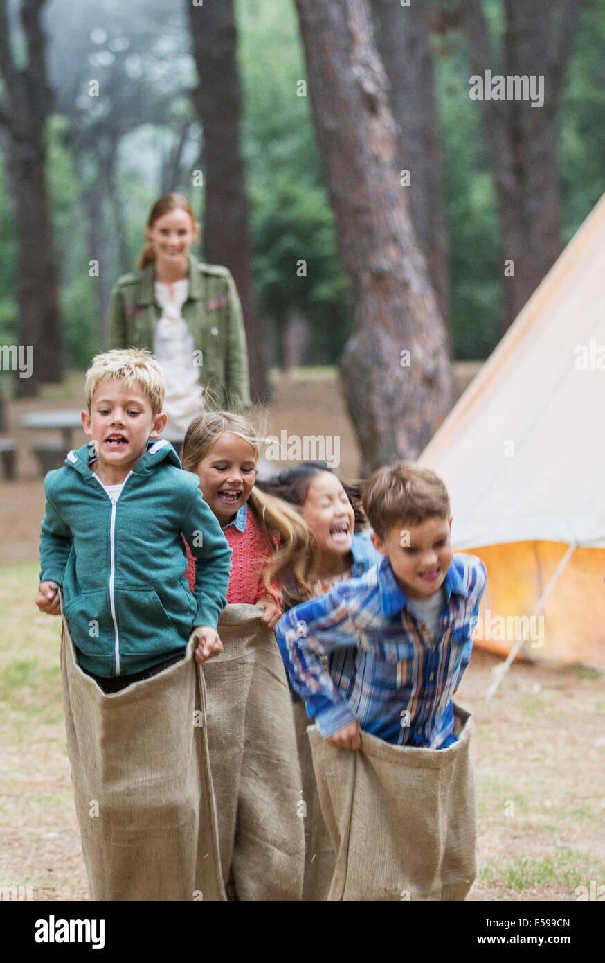 Kinder mit Sackhüpfen auf Campingplatz Stockbild