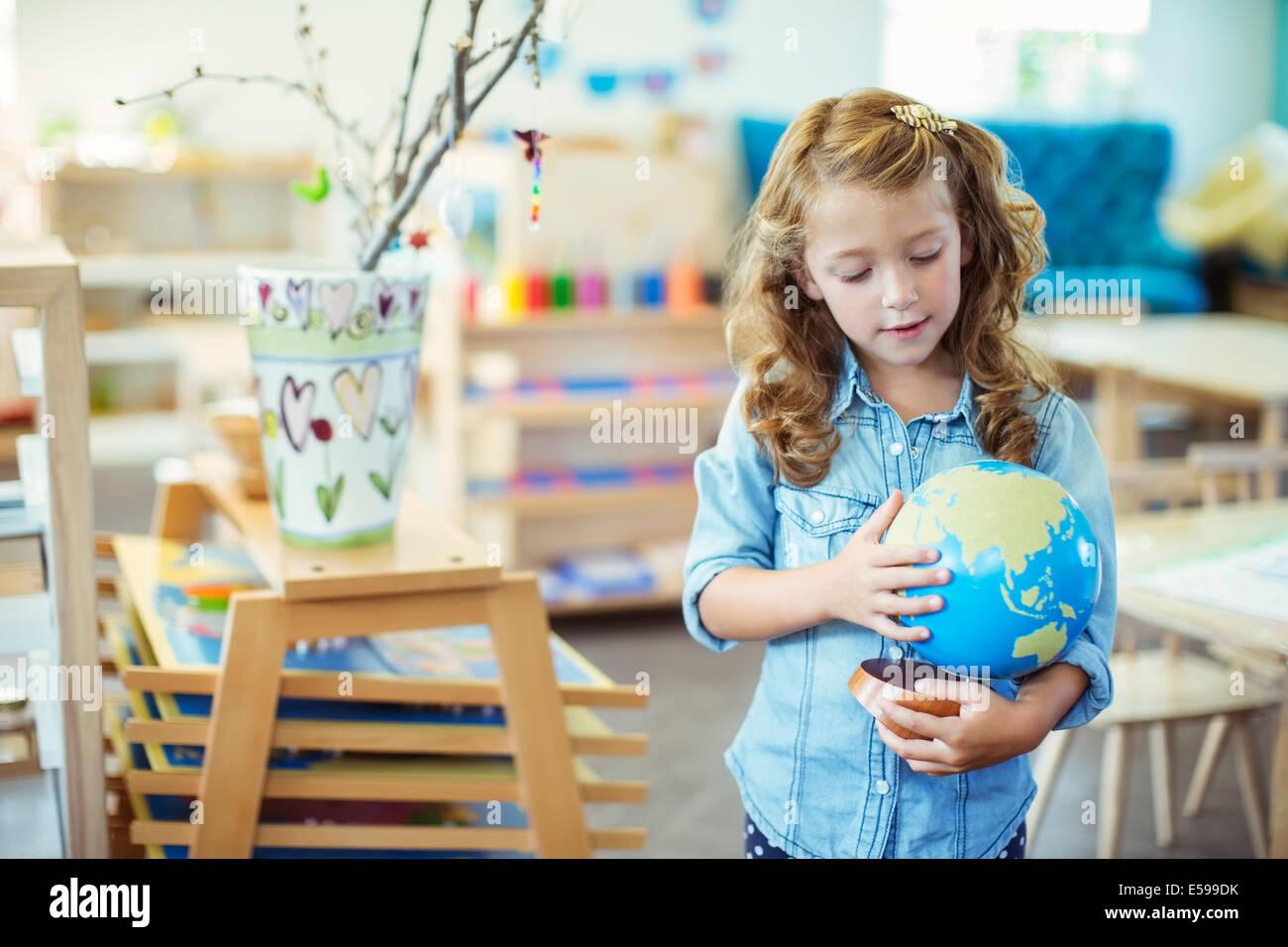 Schüler untersuchen Globus im Klassenzimmer Stockbild