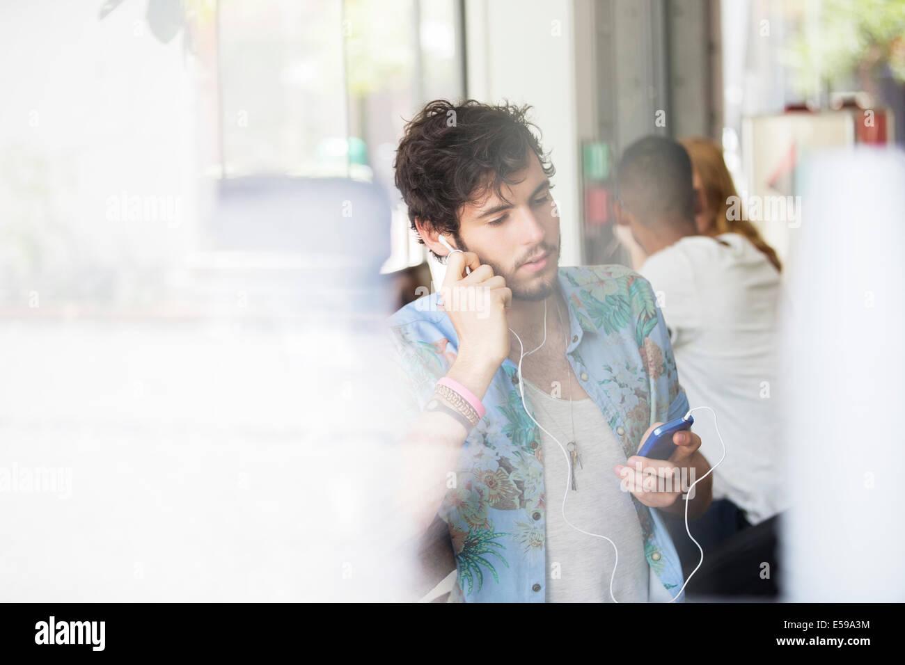 Mann, anhören von MP3-Player im café Stockbild