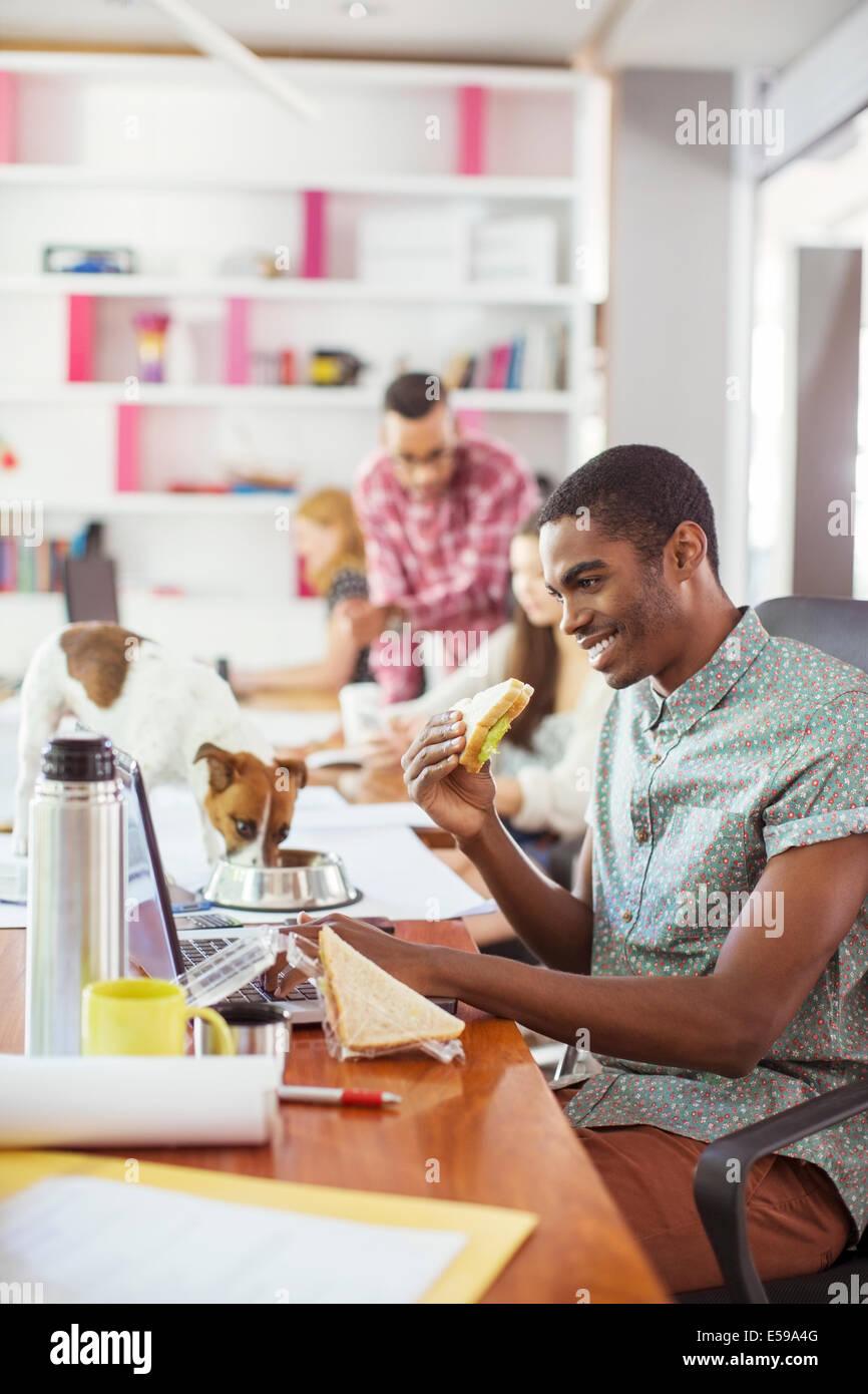 Mann, Essen und arbeiten auf Tablet-Konferenz Stockbild