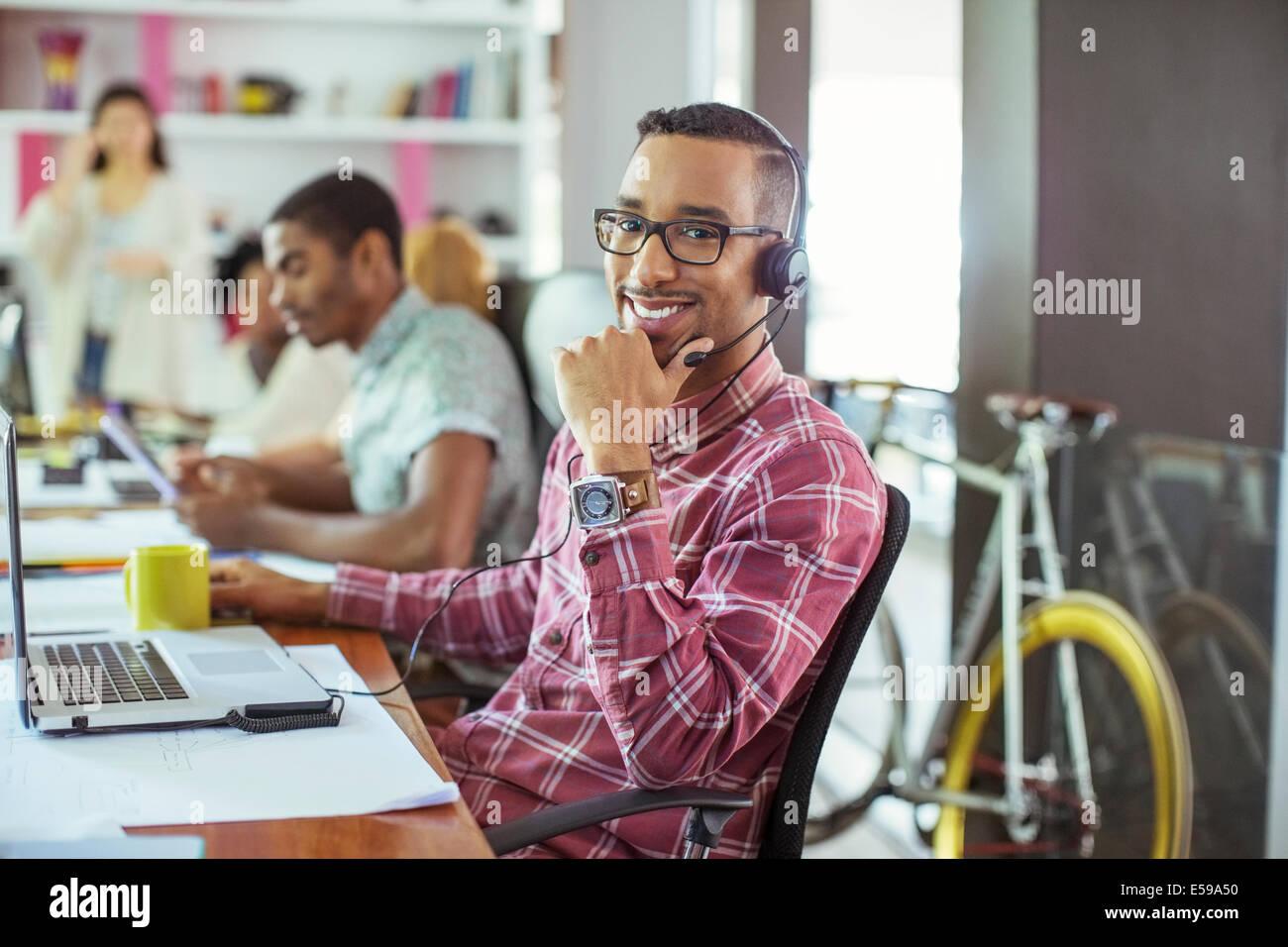 Mann lächelnd am Schreibtisch im Büro Stockbild
