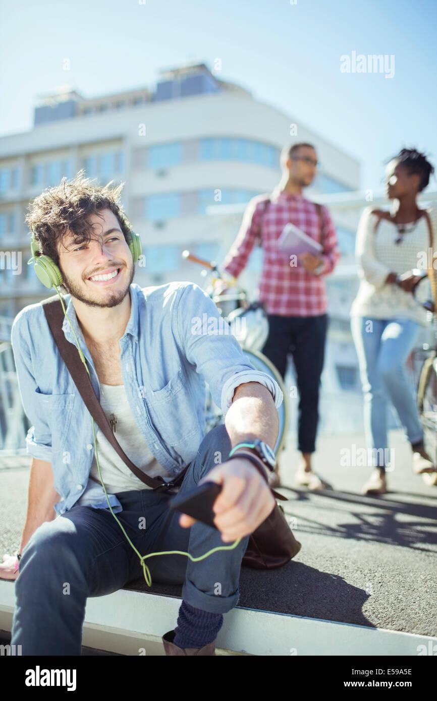 Mann, anhören von MP3-Player auf Stadtstraße Stockbild