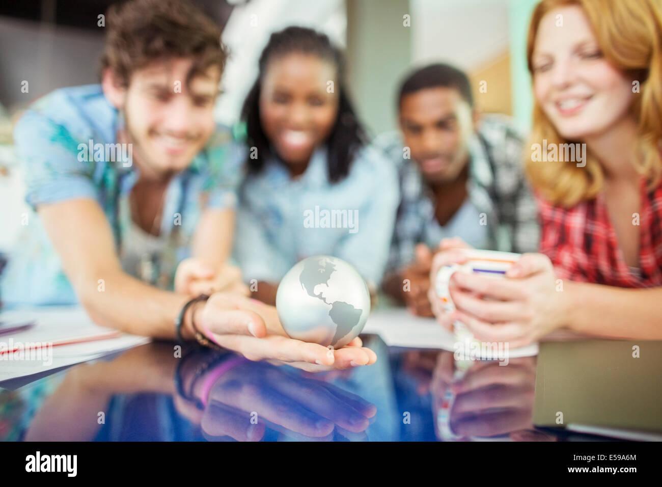 Menschen untersuchen Globus im Büro Stockbild