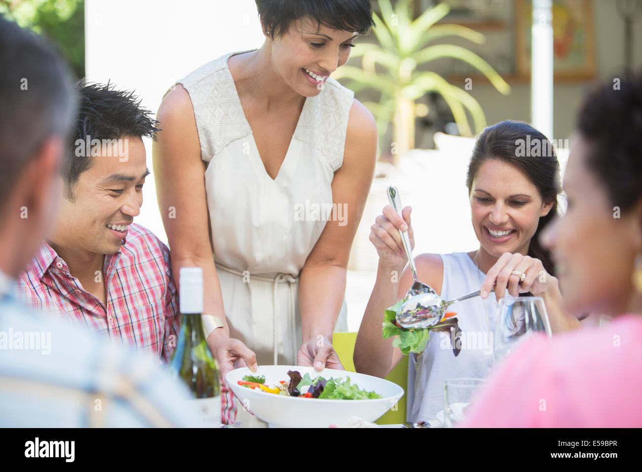 Frau mit Freunden am Tisch im freien Stockbild