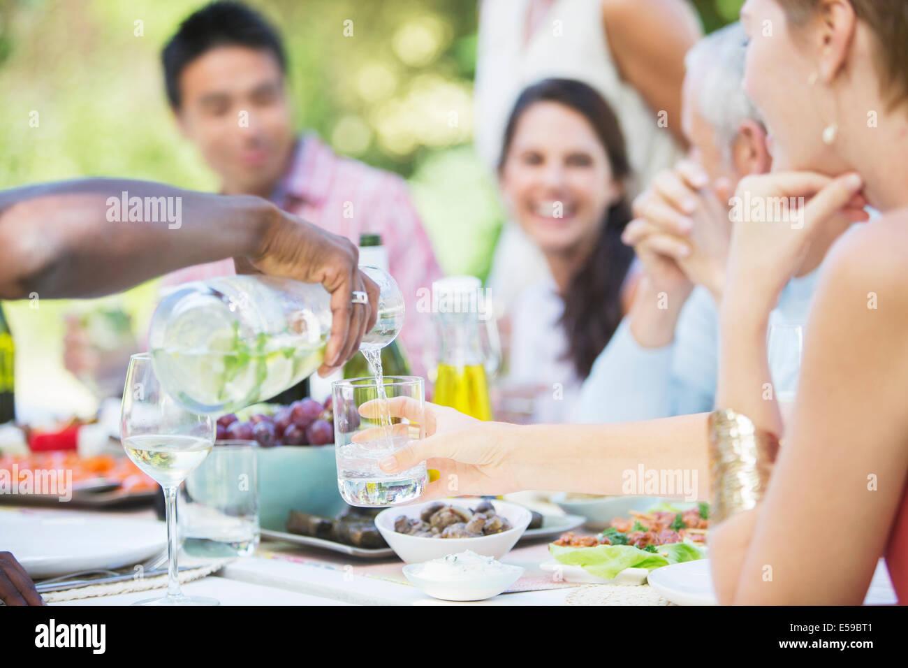 Freunde, die gemeinsam im Freien essen Stockbild