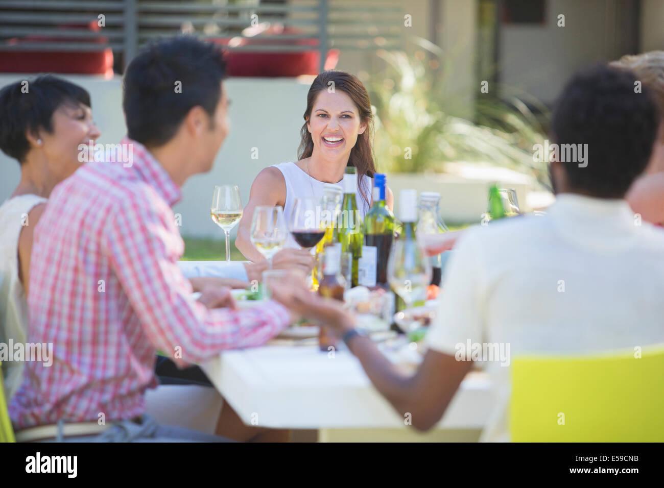 Freunde, die gemeinsam am Tisch im Freien entspannen Stockbild