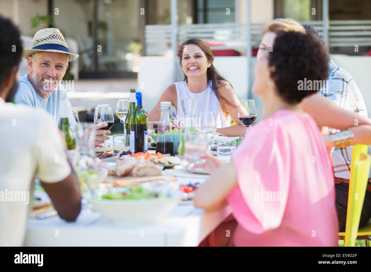 Freunde am Tisch im Freien entspannen Stockbild