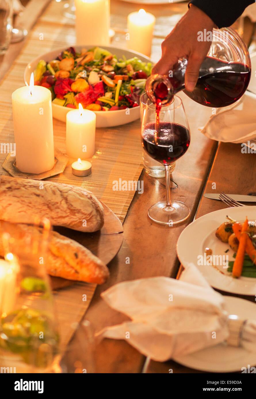 Frau gießt Wein bei Dinner-party Stockbild