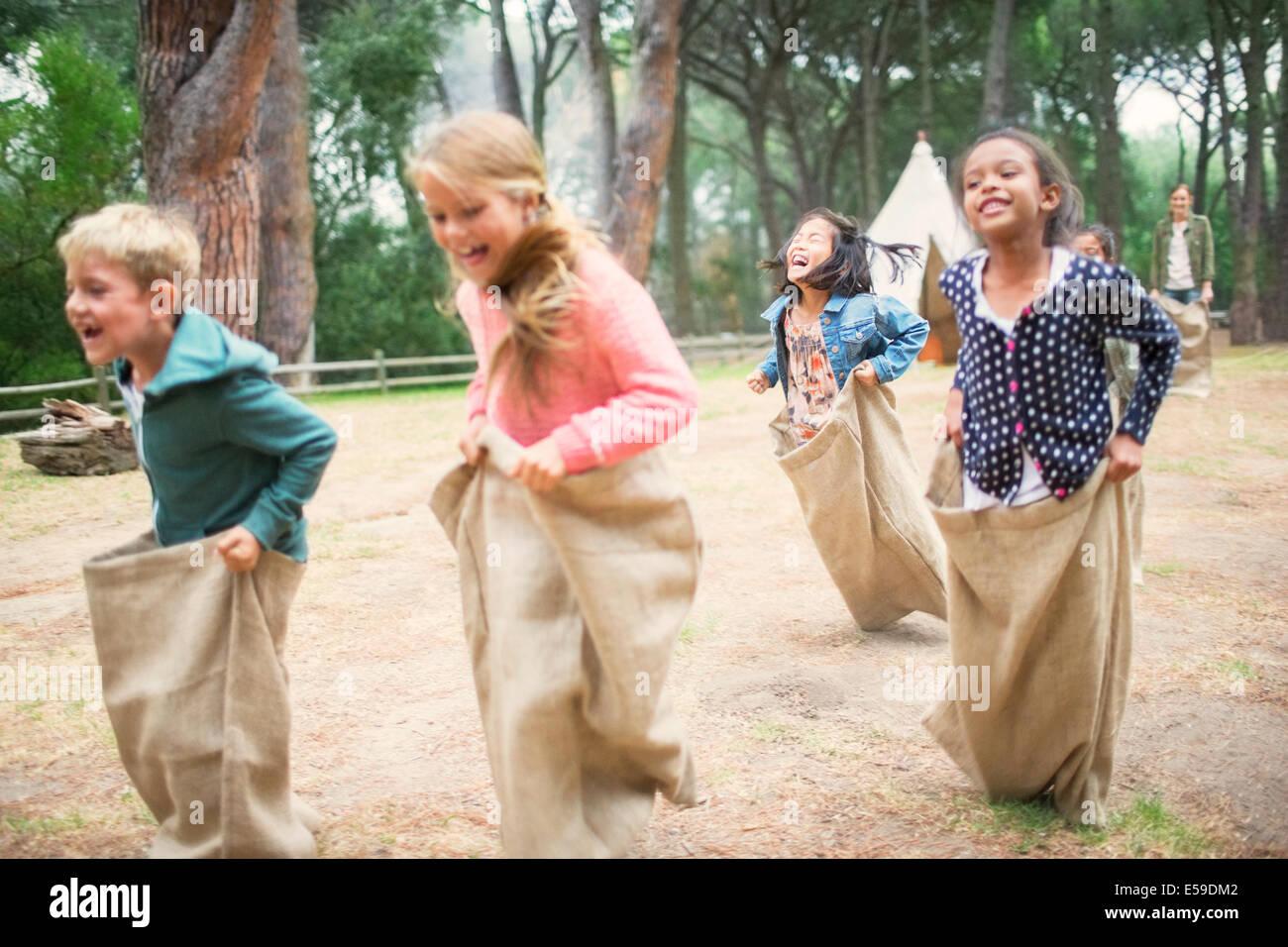 Kinder mit Sackhüpfen im Feld Stockfoto