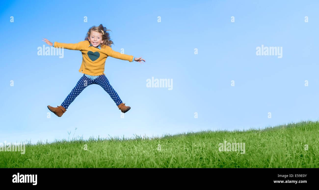 Mädchen springen vor Freude auf grasbewachsenen Hügel Stockbild