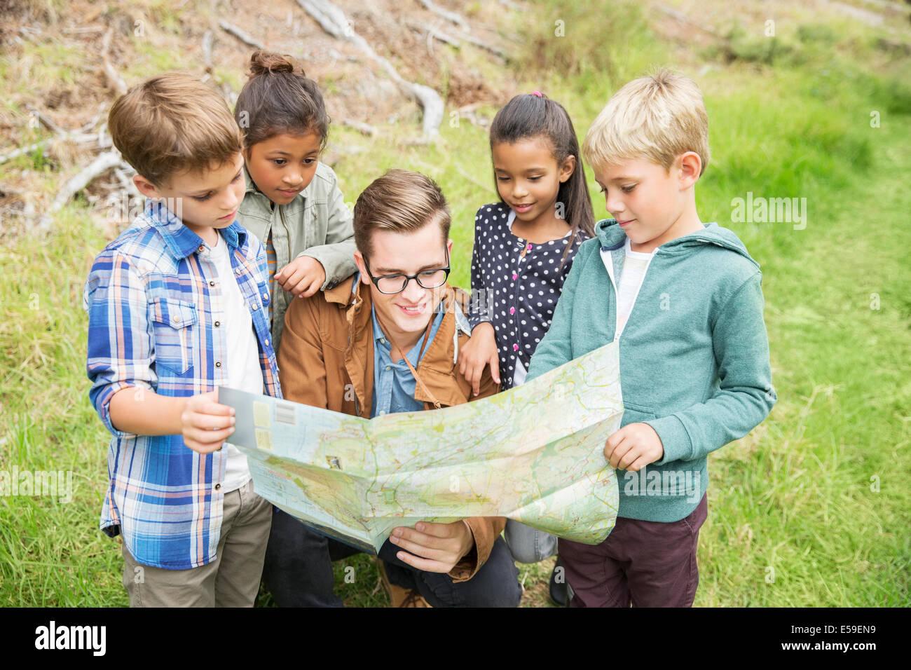 Schüler und Lehrer lesen Karte im freien Stockbild