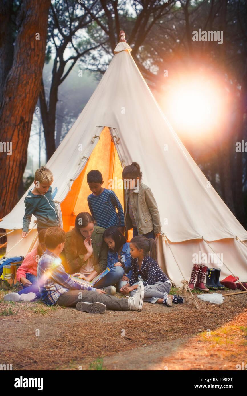 Schüler und Lehrer lesen im Tipi auf Campingplatz Stockbild