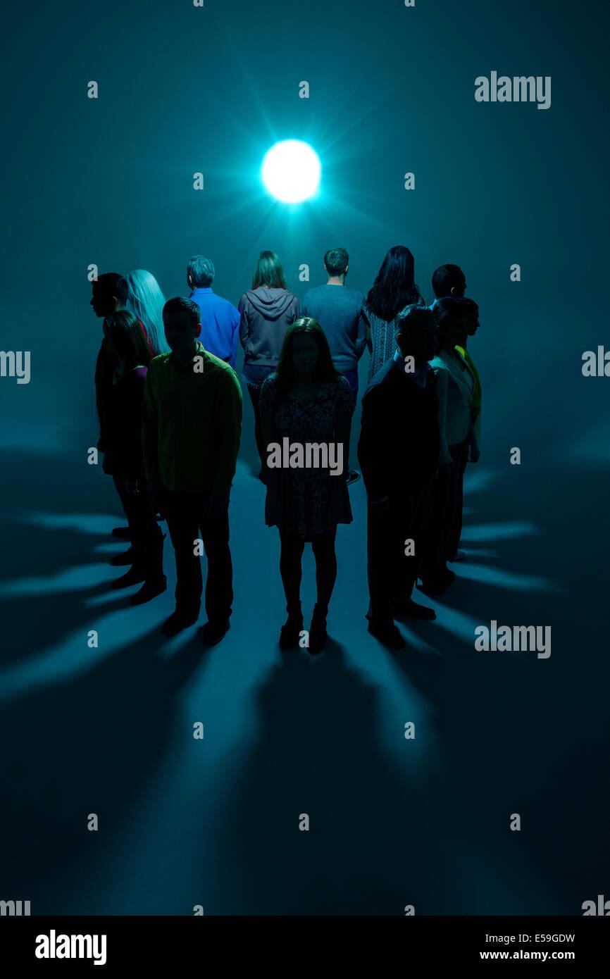 Gruppe mit Rücken zum hellen Licht Stockbild