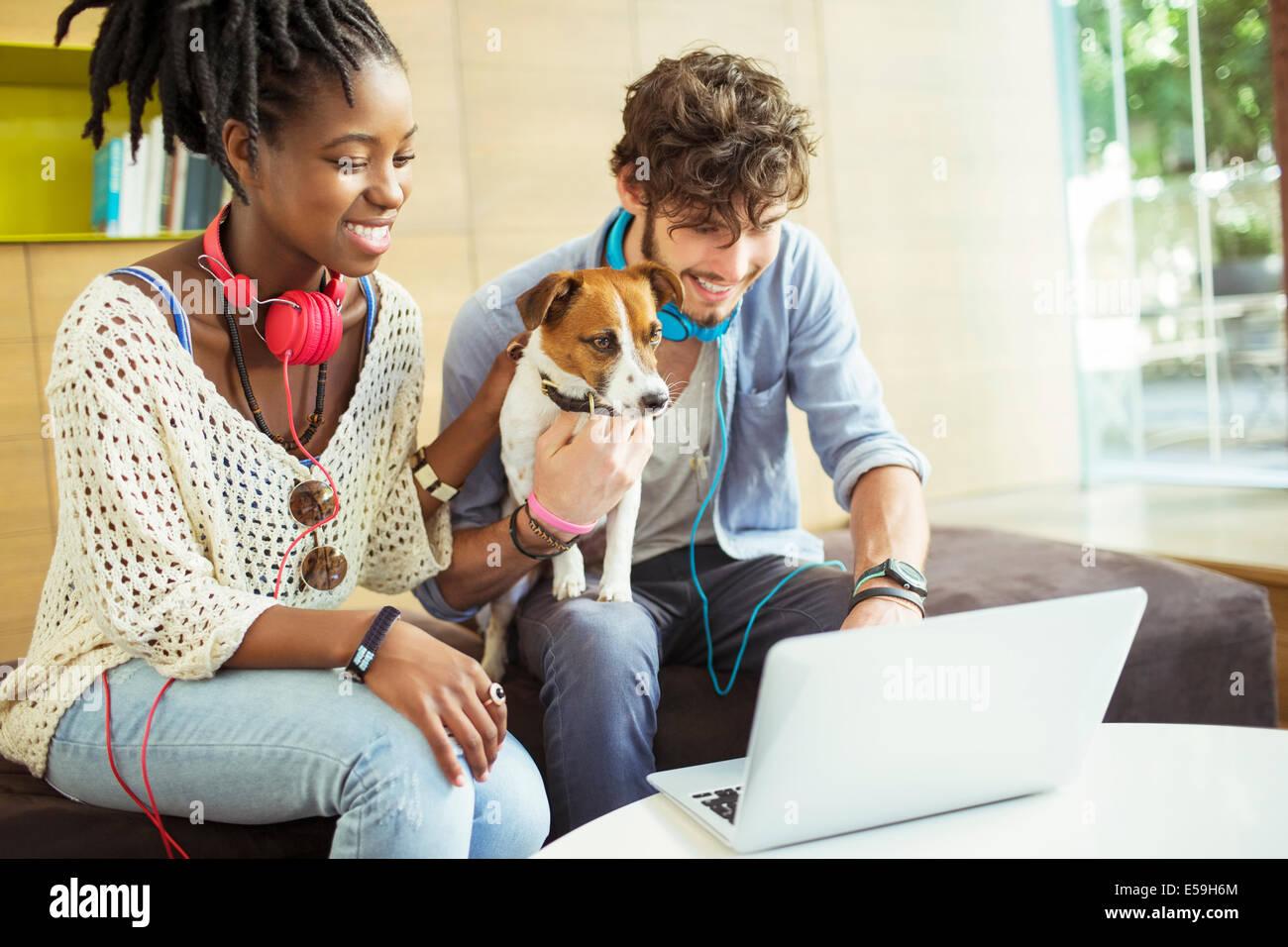 Freunden und Hund arbeiten am Laptop im Büro Stockbild