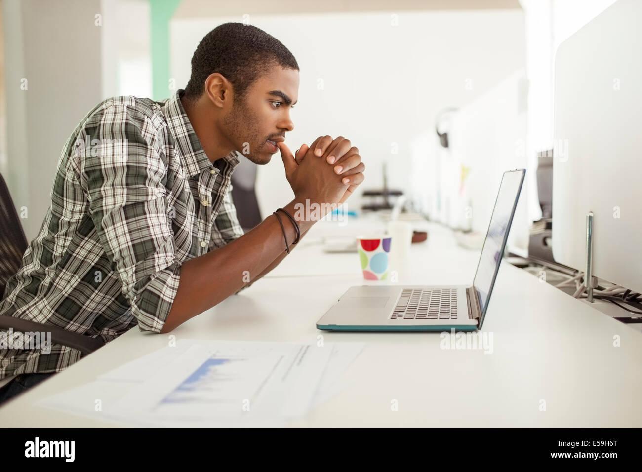 Mann arbeitet am Laptop im Büro Stockbild