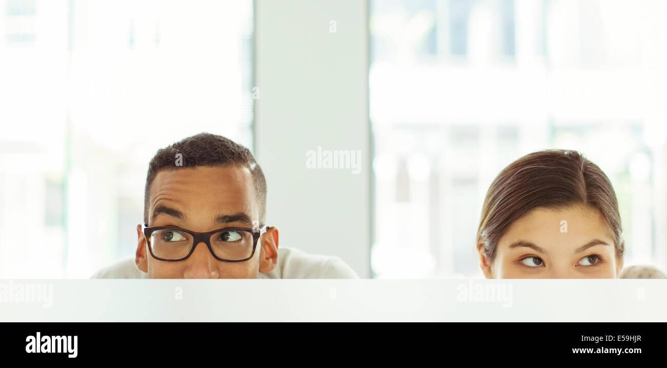 Menschen peeking über Kabine im Büro Stockbild