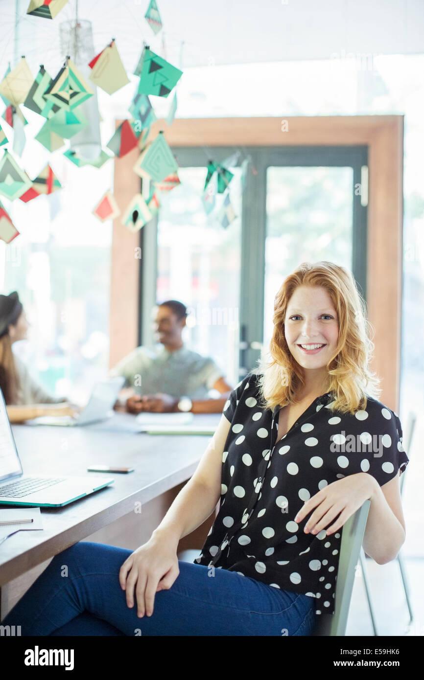 Am Konferenztisch im Büro lächelnde Frau Stockbild