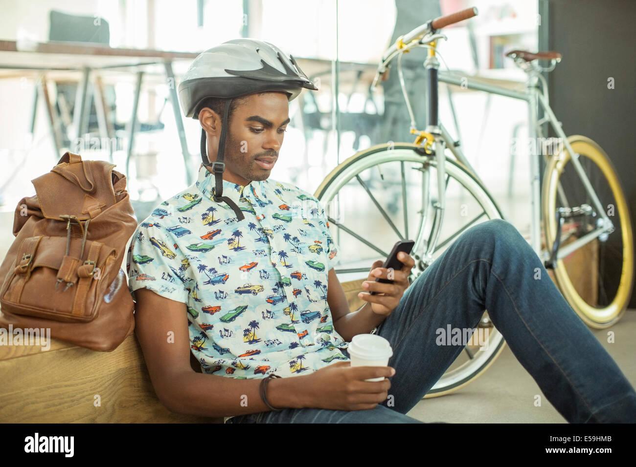 Mann in Fahrradhelm mit Handy im Büro Stockbild