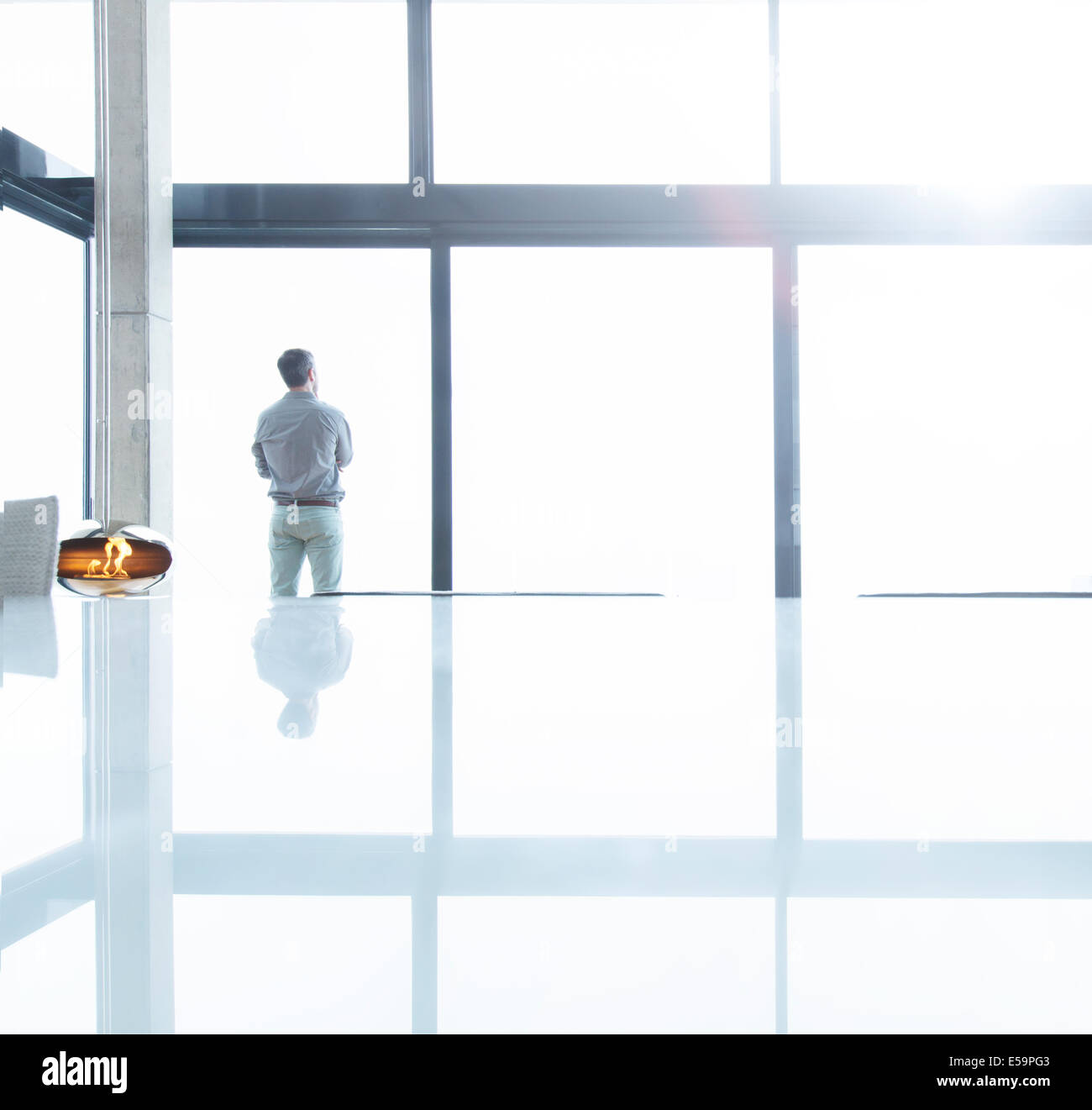 Geschäftsmann am Bürofenster stehen Stockbild