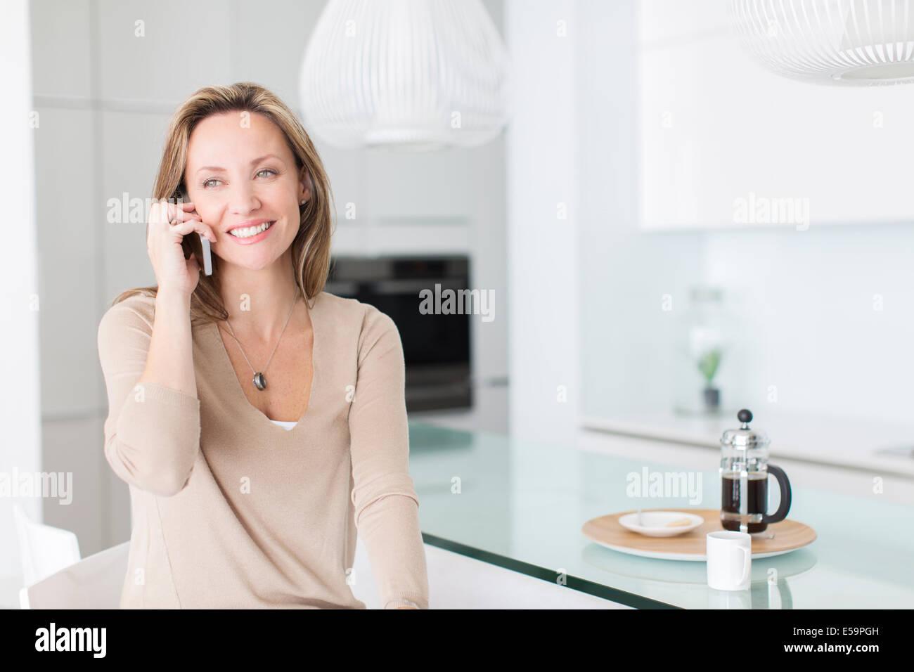 Frau am Handy am Frühstückstisch Stockbild