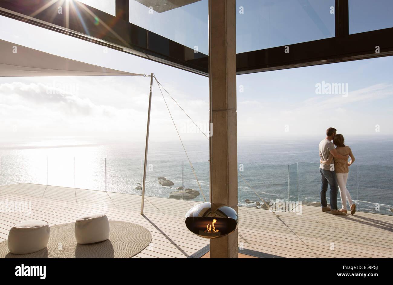 Paar auf Balkon des modernen Hauses stehend Stockbild