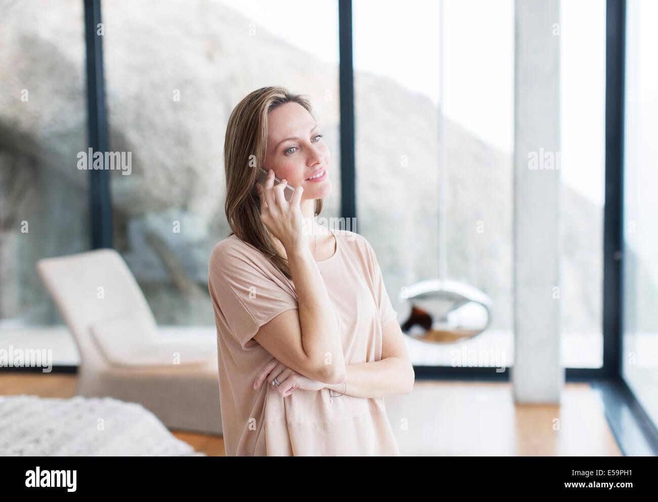 Frau am Handy im modernen Wohnzimmer Stockbild