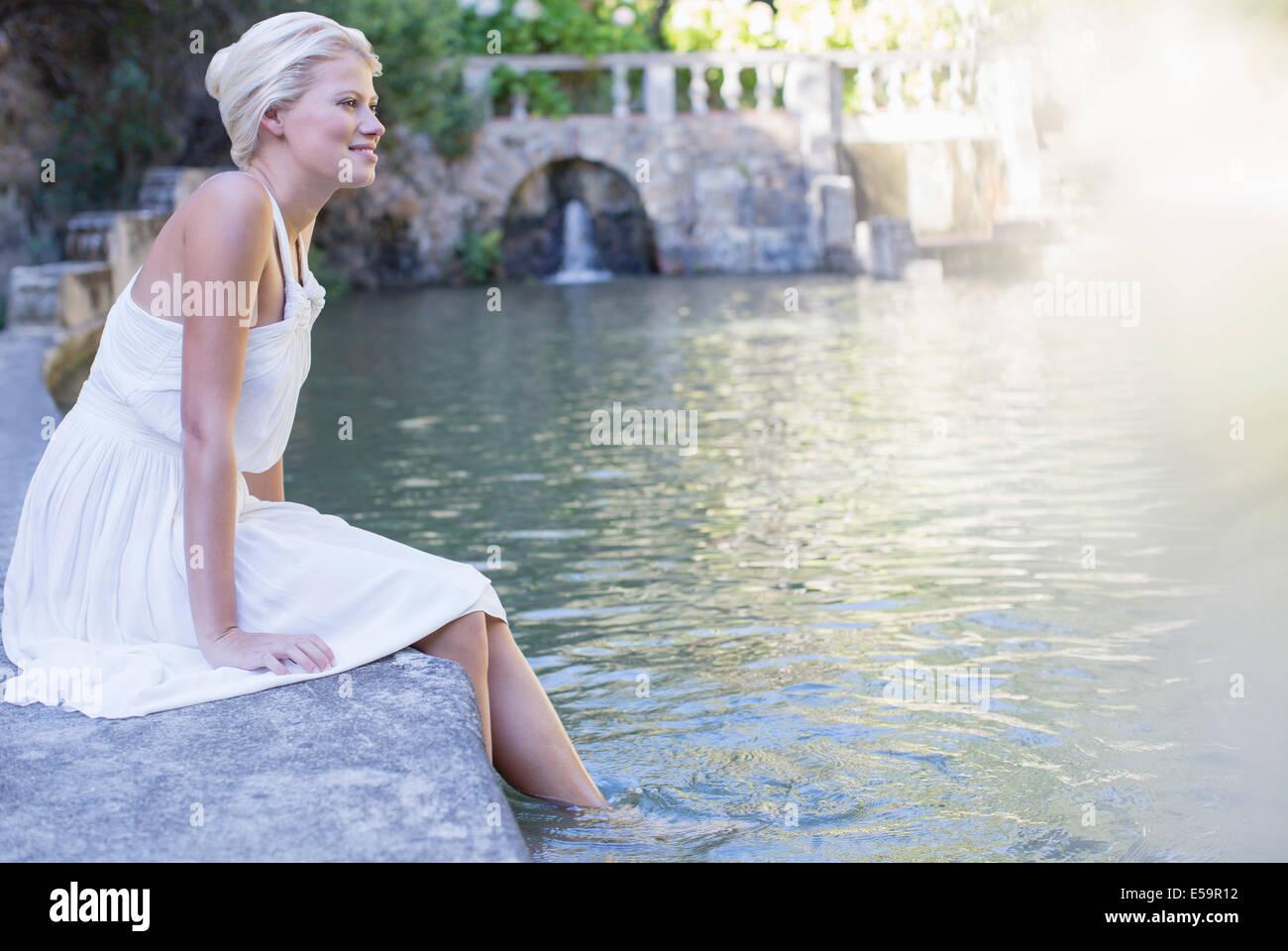 Frau baumelnden Füße im pool Stockbild