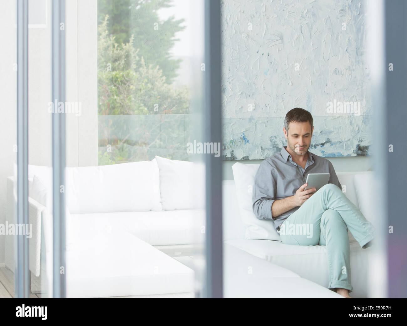 Mann mit digital-Tablette auf sofa Stockbild