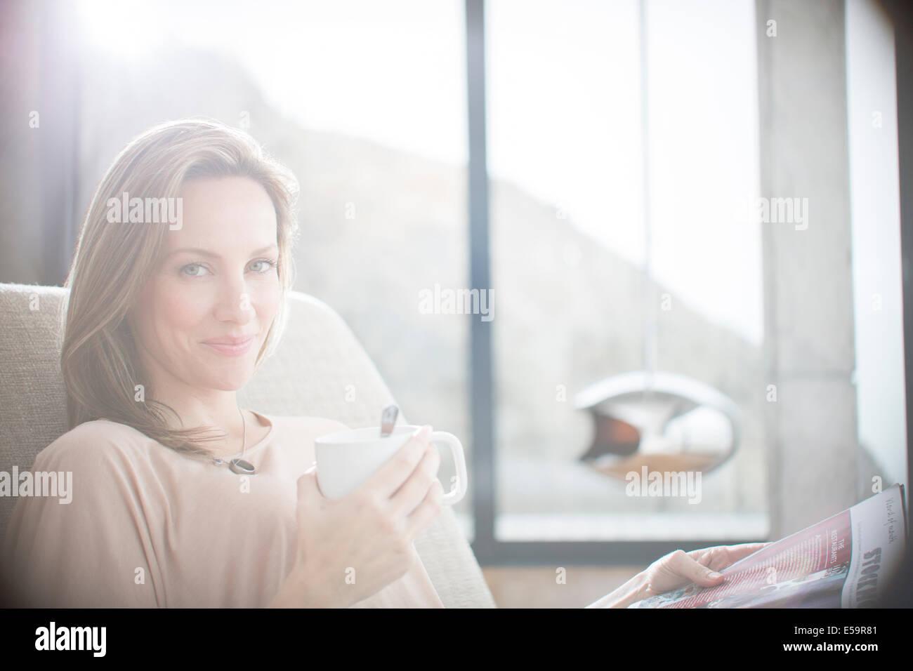 Frau, die Tasse Kaffee auf sofa Stockbild