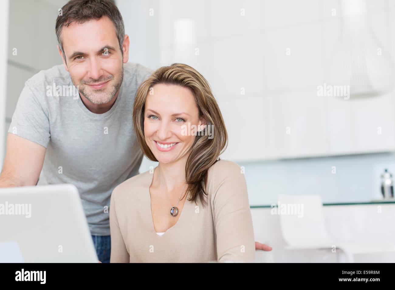 Paar lächelnd auf laptop Stockbild