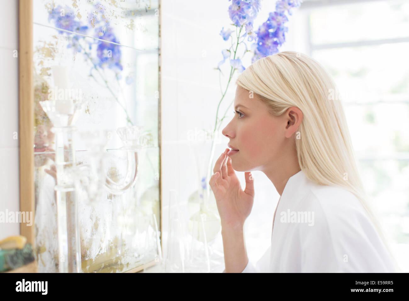 Frau, die selbst im Badezimmerspiegel bewundern Stockbild