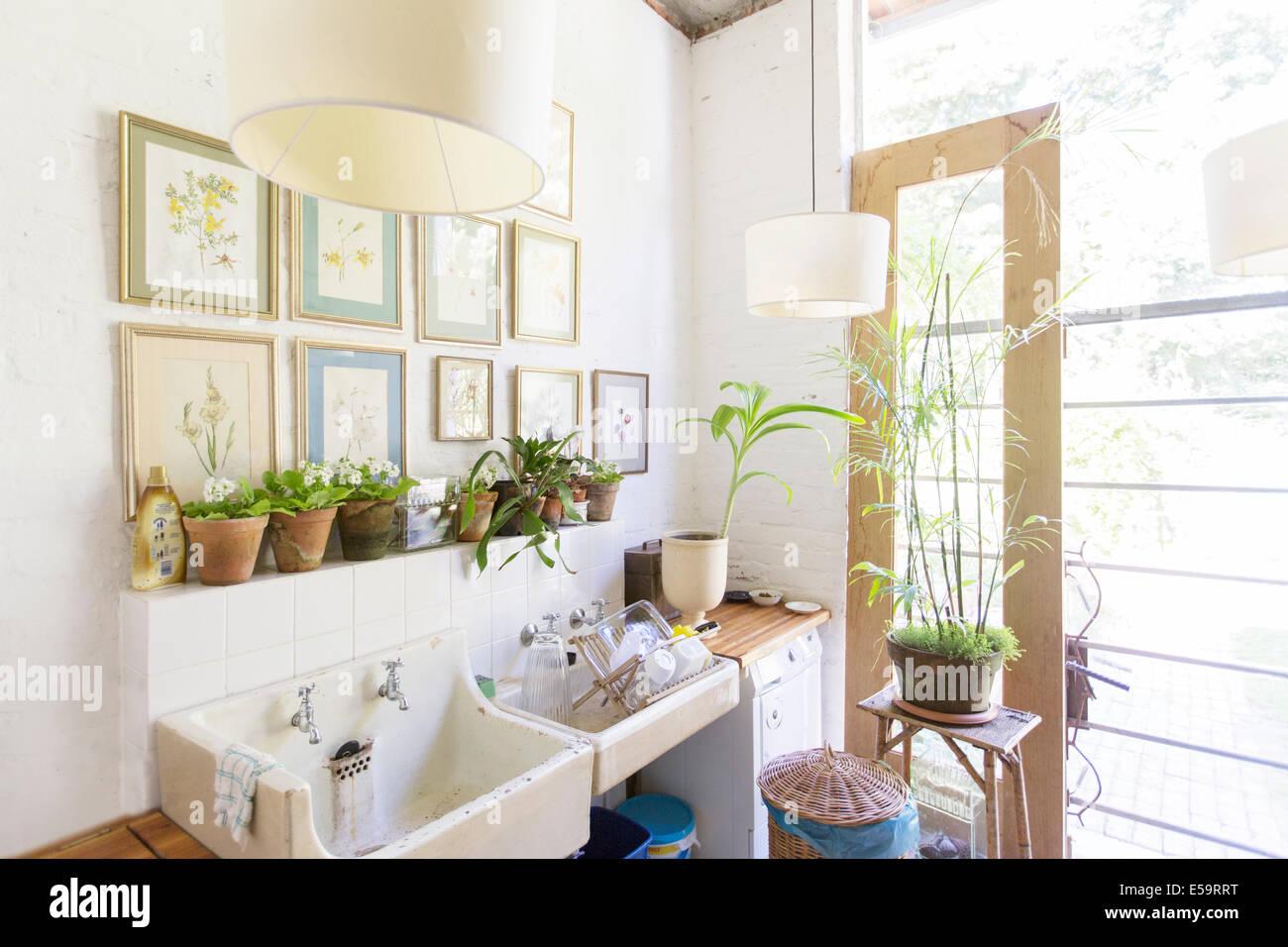 Wandbehänge und Lichter über rustikale Küchenspüle Stockbild