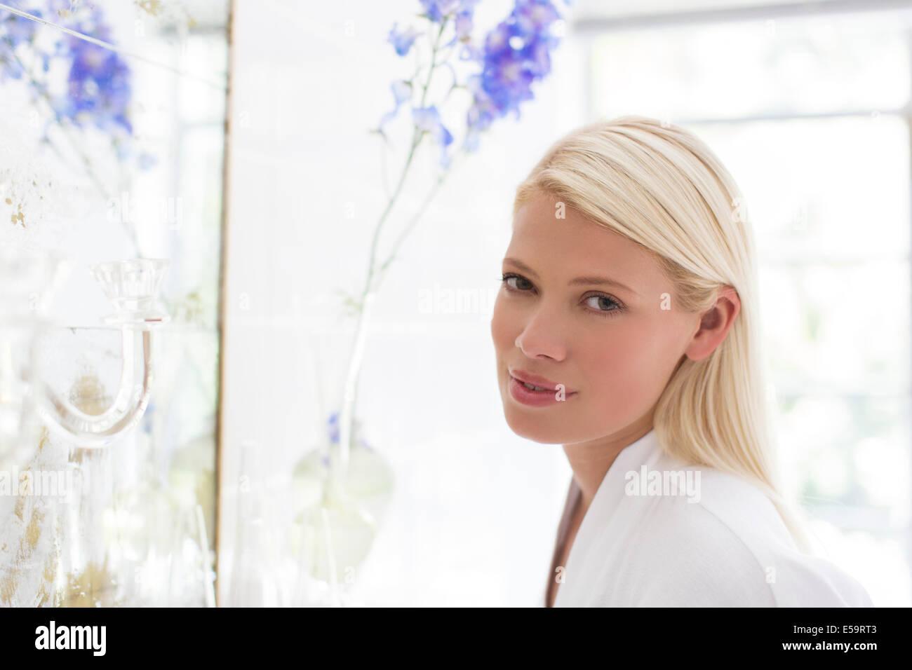 Frau stehend am Badezimmerspiegel Stockbild