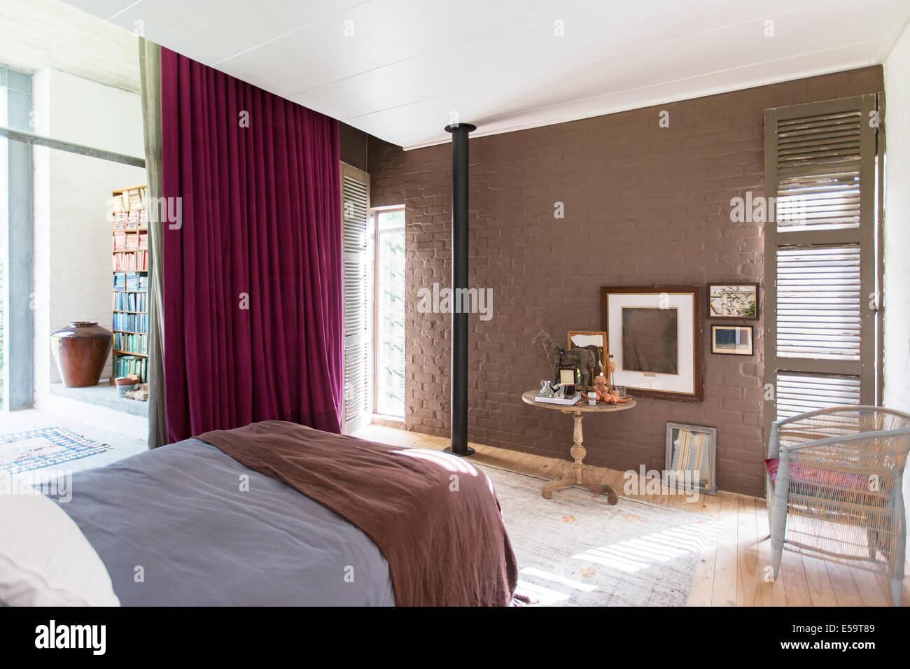 Bett, Beistelltisch und Bilder im rustikalen Schlafzimmer Stockbild