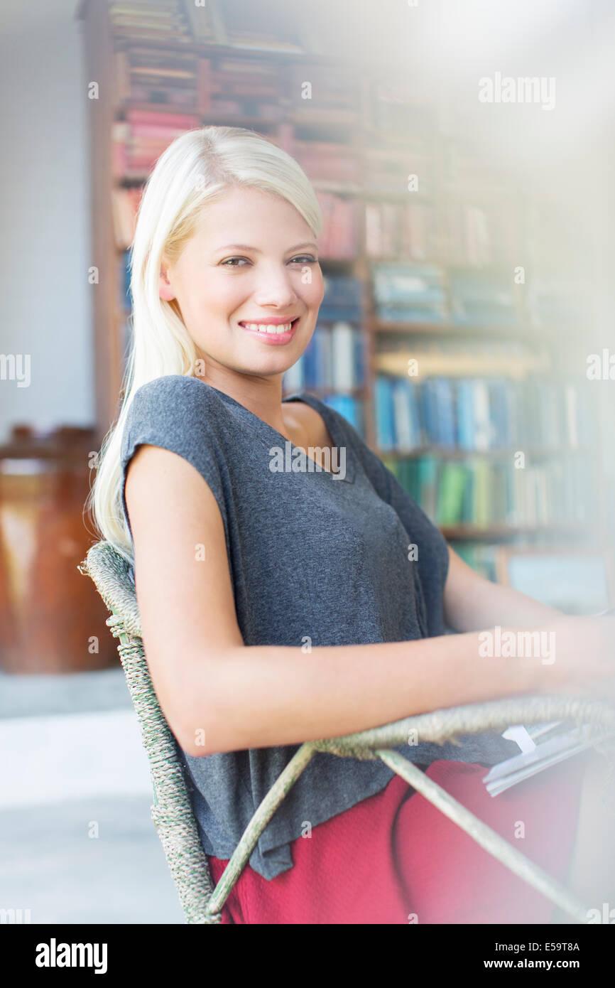 Frau im Sessel lächelnd Stockbild