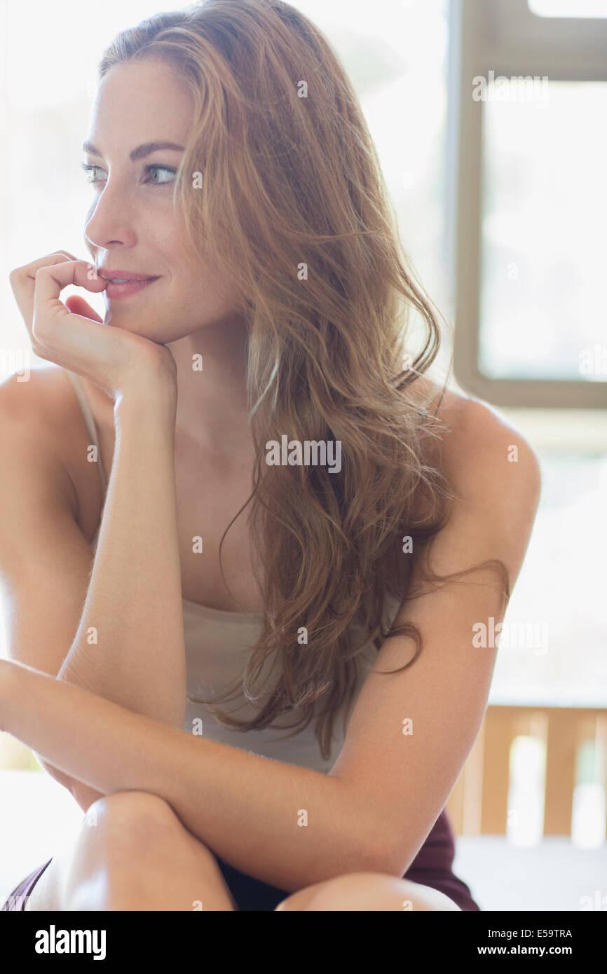 Frau sitzt auf dem Bett Stockbild