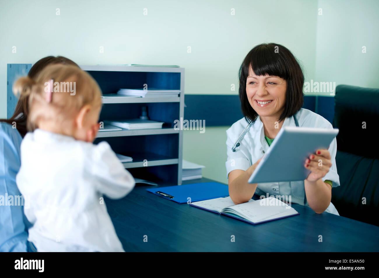 Arzt zeigt Mutter Befunde auf dem Tablet, Debica, Polen Stockbild