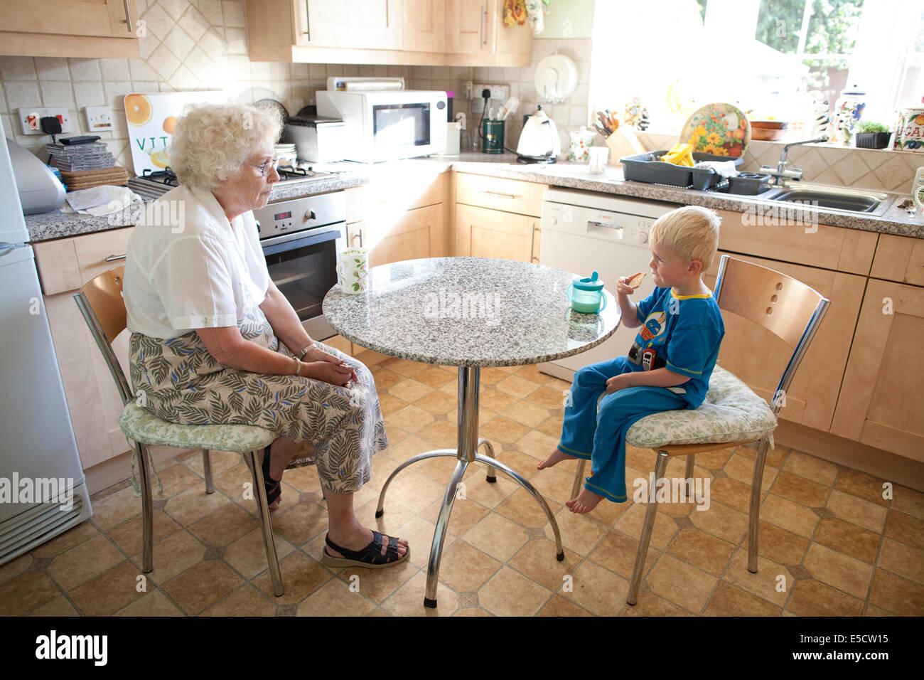 Oma mit ihrem Enkel (3 Jahre) am Tisch sitzen während er eine Tasse Milch trinkt und einen Keks, Vereinigtes Stockbild