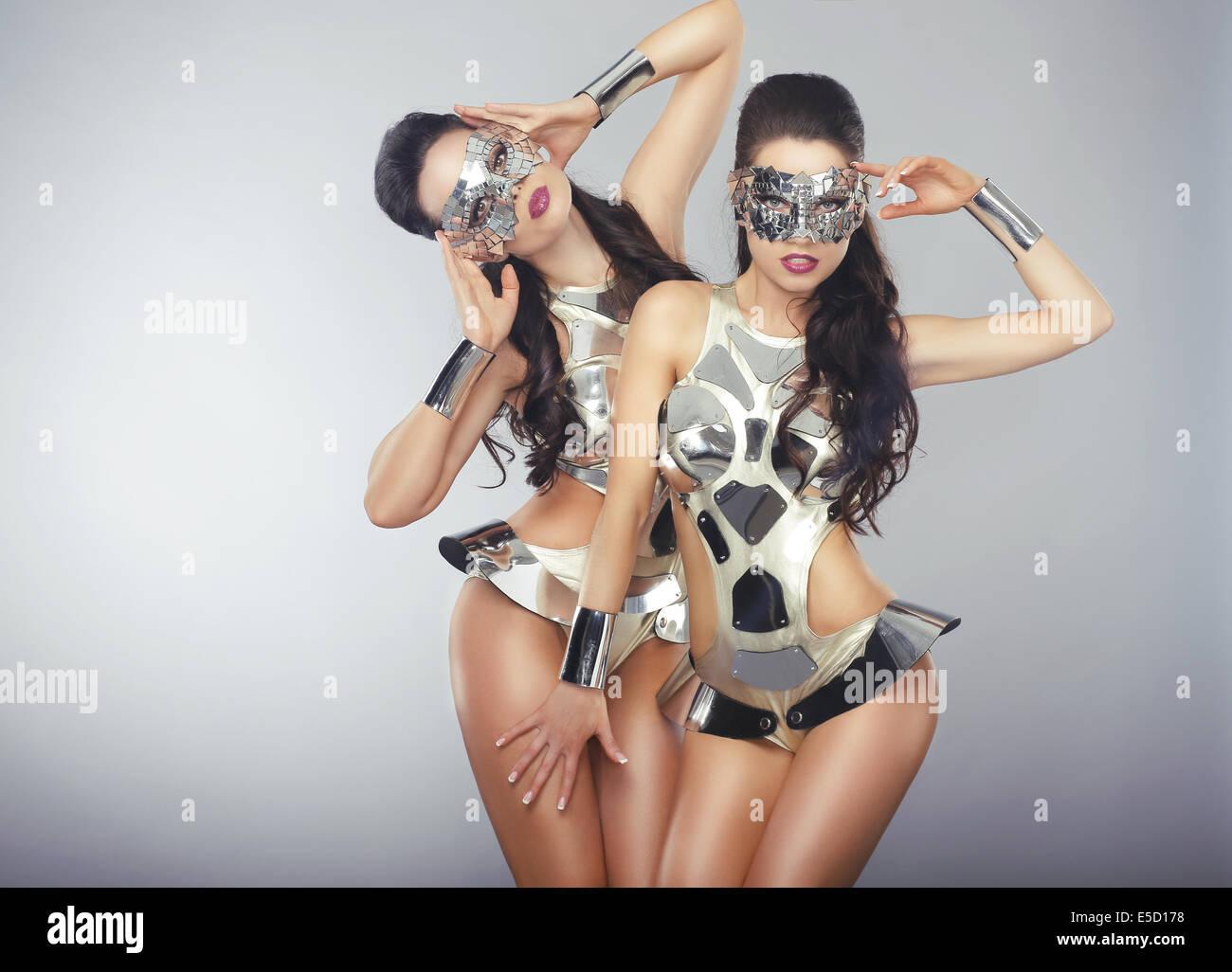 Vogue. Menschen in funkelnden kosmischen Cyber-Kostümen gestikulieren Stockbild
