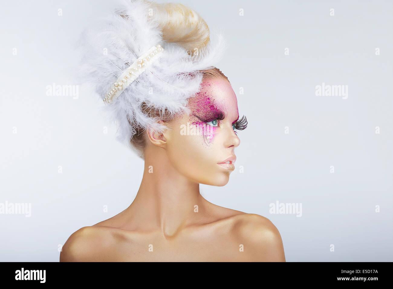Kreativität. Glamouröse Mode-Modell mit ausgefallenen Frisur mit Federn Stockbild