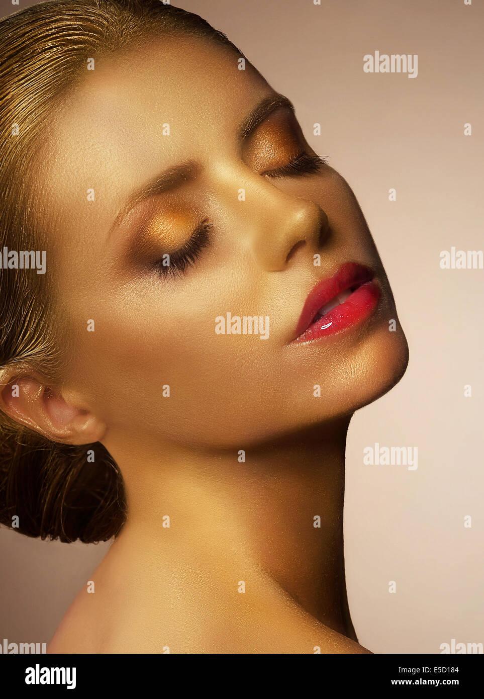 Bodypainting. Vergoldete Frau ins Gesicht. Ausgefallene Golden Make Up Stockbild