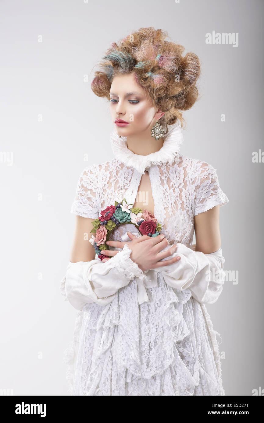 Persönlichkeit. Luxuriöse Frau mit Blumen in Abend-Kostüm Stockbild