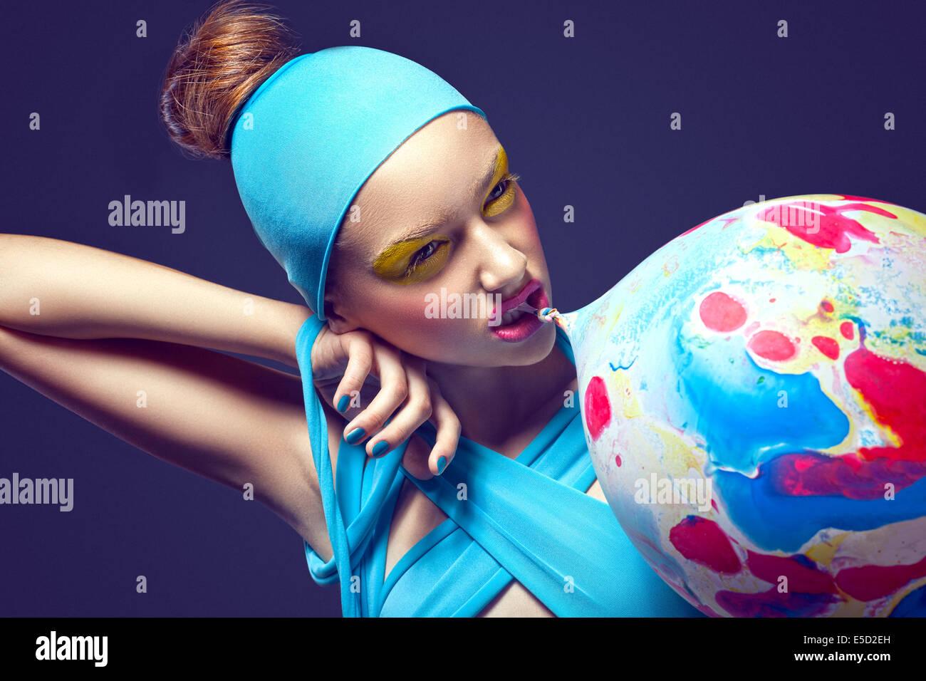 Groteske. Exzentrische Frau mit Phantasie theatralisch Make-up und Luftballon Stockbild